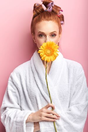 Young caucasian woman holding daisy yellow flower isolated over pink background. Redhead model closed mouth with flower. Female wearing white bathrobe, curlers on hair after shower. Natural beauty 写真素材 - 132747697