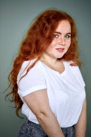 Young caucasian girl with red hair wearing white t-shirt and shorts, posing, look at camera. Red curly long hair, model, plus size