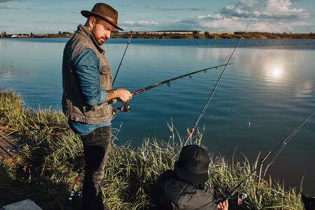 Father explained son how fish. He look at him. Teen son try fish well.