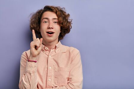 Cheerful handsome boy looking at camera with positive face, opens mouth, pointing finger up, gets an idea, violet background, portrait