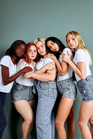 Full-length portrait of five beautiful women in jeans standing together isolated over grey background