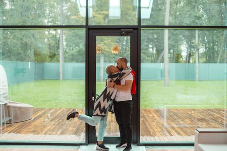 Beautiful caucasian couple kissing in new countryhouse. Background panoramic window