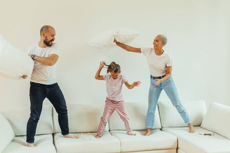 Positive Caucasian family fighting with pillows on bed. Jumping and having fun children and parents. Happy family concept. White colors Stockfoto - 133274765