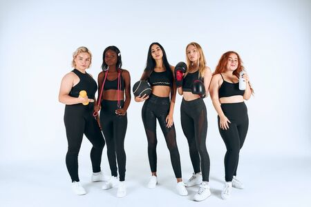 Sportive girls in sport wearing stand together with boxing gloves, dumbbells and other sportive things, look at camera isolated, white background