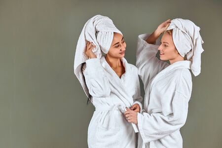 Young caucasian girls wearing white bathrobe and towel, hug each other and look, posing islated over grey background. Natural beauty, friendship 版權商用圖片
