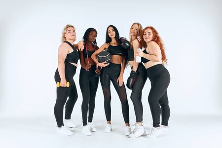 Five smiling multiethnic women wearing sportive leggins and topics holding fitness ball, boxing gloves and other things isolated over white background Stockfoto