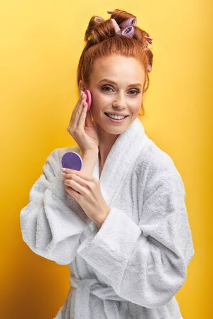 Portrait of beautiful woman in bathrobe isolated over yellow background, holding beauty sponges near face. Natural beauty concept