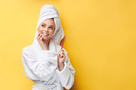 Dreamy caucasian girl within temptation of celebration, holding magic wand. Wearing bathrobe and towel, isolated over yellow background