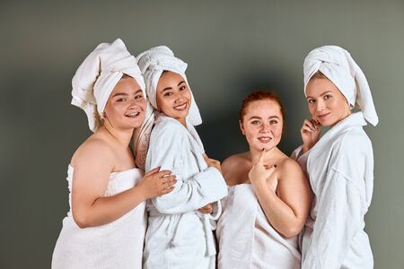 Beautiful young smiling women with perfect skin wearing white bathing towels having fun isolated on grey background 版權商用圖片