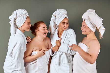 Beautiful young smiling women with perfect skin wearing white bathing towels having fun isolated on grey background. Laugh while looking at each other 版權商用圖片