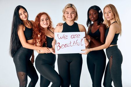 Young attractive girls stand holding poster we are beautiful isolated over white background. Portrait of charming different multiethnic girls