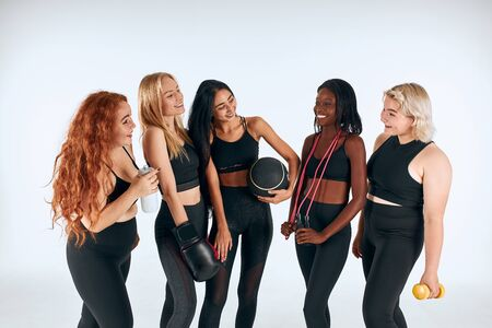 Smiling women in black sportive clothes laughing, look at each other, promote healthy lifestyle, people relationship.