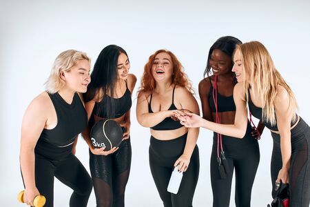 Five attractive girls stand together isolated over white background, smile and talk. Redhaired girl show ring, other girls look and surprised. Different nations, nationalities