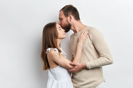 bearded attractive guy kissing his woman on her forehead. close up photo. isolated w Reklamní fotografie