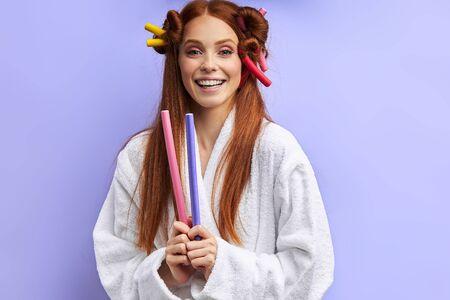 Glückliche junge Frau im Bademantel mit Lockenwicklern auf dem Haar posiert, Blick in die Kamera. Porträt, über lila Hintergrund isoliert Standard-Bild