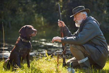 Obedient hunter dog sit with his owner near forest lake after hunting on wild ducks. Good work little friend, dog friend 스톡 콘텐츠