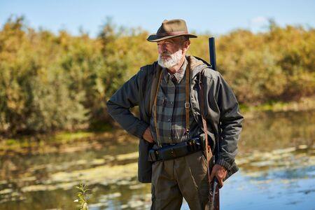 Senior man with gun going to hunt on wild ducks on lake. Male looking away