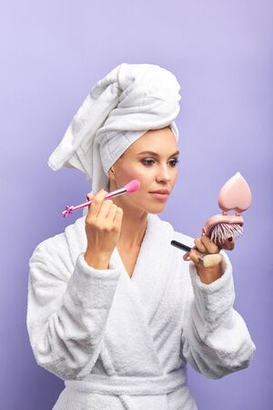 Portrait of beautiful caucasian woman in bathrobe and towel holding small mirror and makeup brushes. Applying make up, purple isolated background