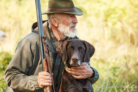 Caucasian mature man with gun and dog sit searching prey. Bearded man in hunting clothes. Autumn