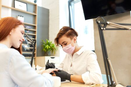 Positive smiling girl in shirt came in salon to do manicure. White shirt on manicurist Imagens