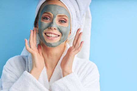 Attractive charming female applied mask on face. Cosmetic procedures, isolated over blue background.