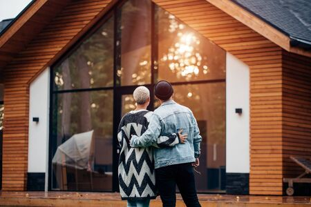 Rear view on lovely couple looking at new countryhouse. Excited man and woman, smile and happy together Stock Photo