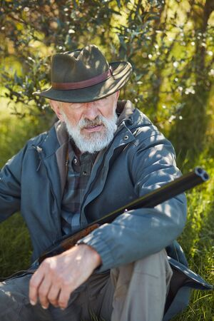 Bearded man with gun sit having rest after good hunting. Forest, grass background. Hunting, people concept