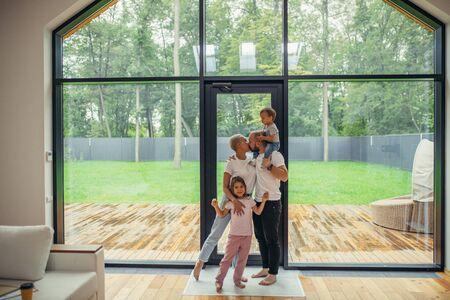 Genitori innamorati che si baciano. Bella e felice famiglia insieme a casa con finestra panoramica in piedi. Abbracciatevi