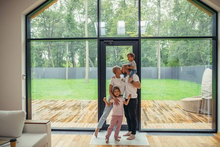 Lovelt parents kissing. Beautiful and happy family together at home with panoramic window standing. Hug each other Reklamní fotografie - 133179701