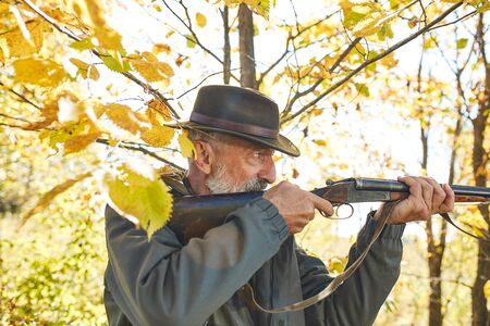 Concentrated hunter holding rifle and waiting for prey, hunter shooting in autumn forest. Hunting season