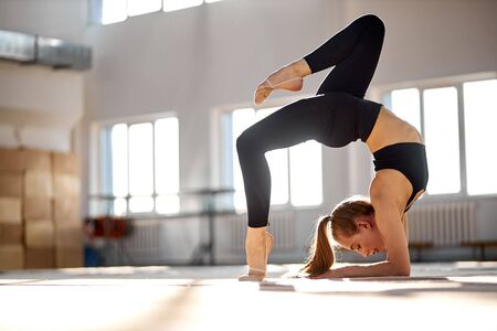 Pretty charming female training and stretching in big, bright room in black leggins and bra, looks away, stands on bridge position, professional sport concept 写真素材
