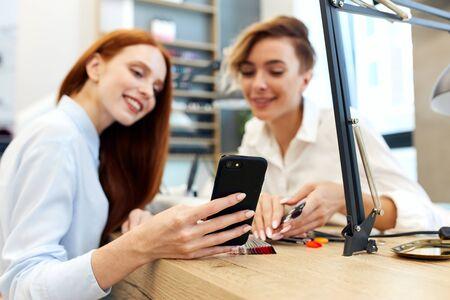 Il padrone e il cliente allegri guardano il telefono su una bella manicure. La ragazza dai capelli rossi vuole una manicure come su uno smartphone.