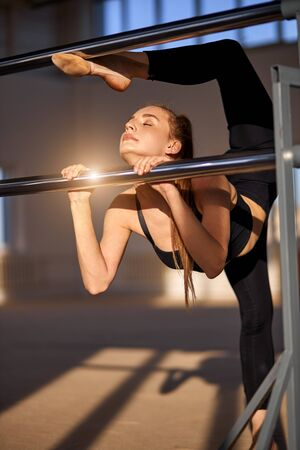 Charming sporty girl actively trains by metal bar, closes eyes with calm face, stretches out, holds ballet bar with both hands, raises leg up in fitness club, gymnasium concept Banco de Imagens