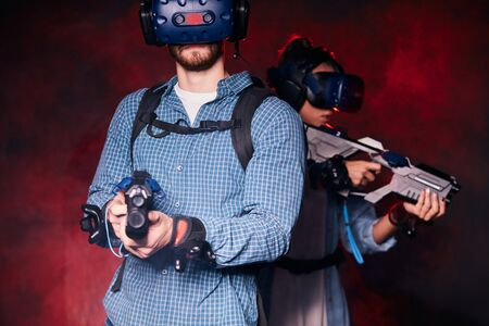 couple adventurers stand together back to back holding virtual guns, in fight. Isolated smoky background, red neon light Stok Fotoğraf