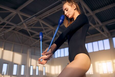 Charming beautiful girl training in storts hall, keeping dark blue gymnastics clubs in hands,looks down, shot from below, active lifestyle concept