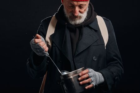 Mature grey bearded man holding iron pan and soup ladle. Try to find some food on the bottom of pan. Isolated over black background