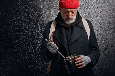 Senior grey bearded man holding iron pan and soup ladle. Try to find some food on the bottom of pan. Isolated over black background
