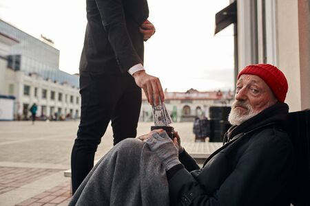 businessman came up and help homeless man sitting on the floor. Help, money donation to vagrant male in the street Reklamní fotografie