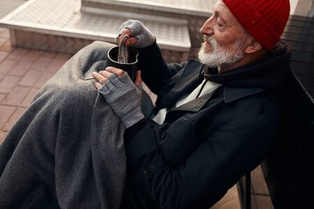 Beggar male sit with jar for money, wearing warm old clothes. Vagrant with grey beard, red hat and grey gloves