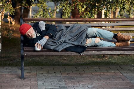 Vagrant male lying on street bench asking for money, for any help. Desperate and lonely homeless man without shelter Stock Photo