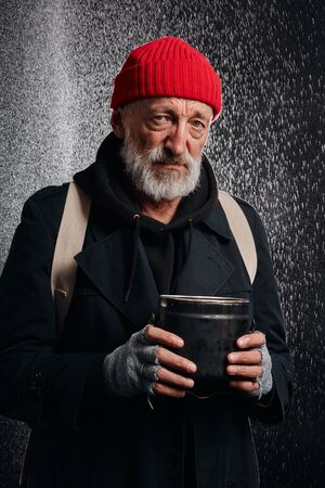 Portrait of homeless man in black street clothes holding iron can for collecting money. Need for help