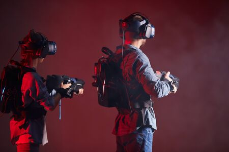 Side view on woman and man holding virtual guns, looking side. Stok Fotoğraf