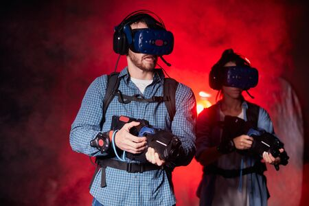 Man and woman using virtual reality headset and weapon in smoky space, red light of the playing club