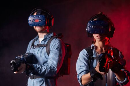 Man and woman with vr guns and headsets standing isolated black background with red neon backlit. entertainmnet, copy space Stok Fotoğraf