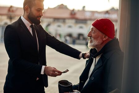 Businessman in tuxedo help to vagrant man sitting on street with rusty money jar. Rich man put one hand on shoulder of homeless person and give one dollar. Kind people, compassion, sympathy Reklamní fotografie