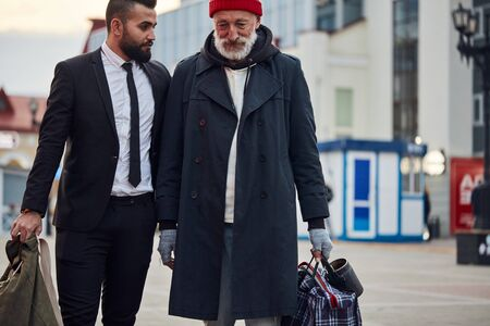 Rich man decided to help poor man. Young bearded man in black suit with beggar senior male. Contrast, different segments of society