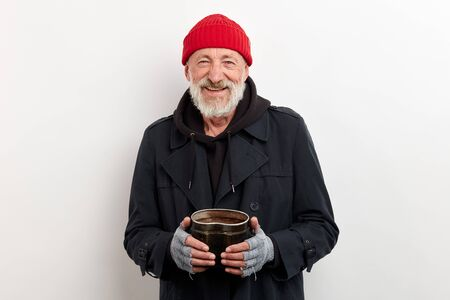 Mature smiling bum in black coat and red cap on head holding iron can for raising money. Isolated over white background