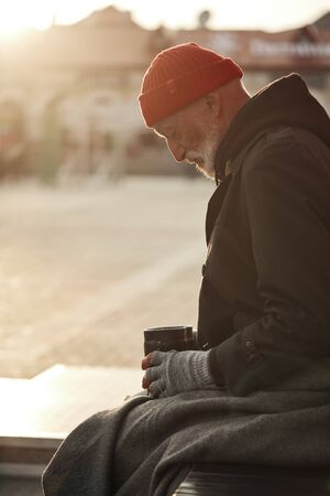 Money ask. Homeless person in street clothes sit head bowed asking for help in cold weather. Poverty