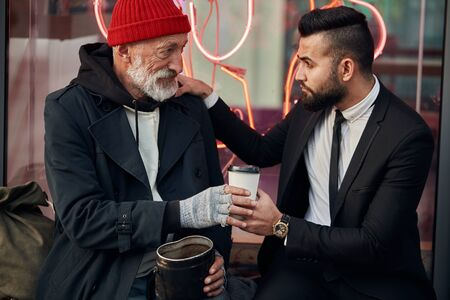 merciful businessman sit next to tramp in red hat and coat, rich man in black tuxedo. Vagrant get coffee from businessman Stock fotó