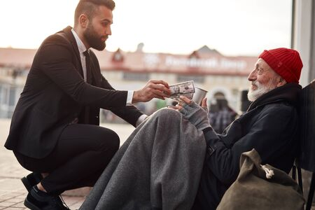 Kind man in suit hunkered down to homeless and give money donation, one dollar bill to beggar male Reklamní fotografie